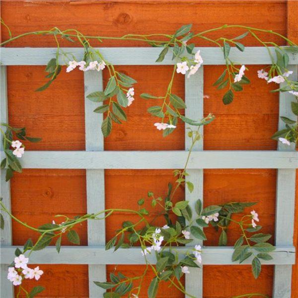 artificial jasmine garland wrapped around an outdoor trellis