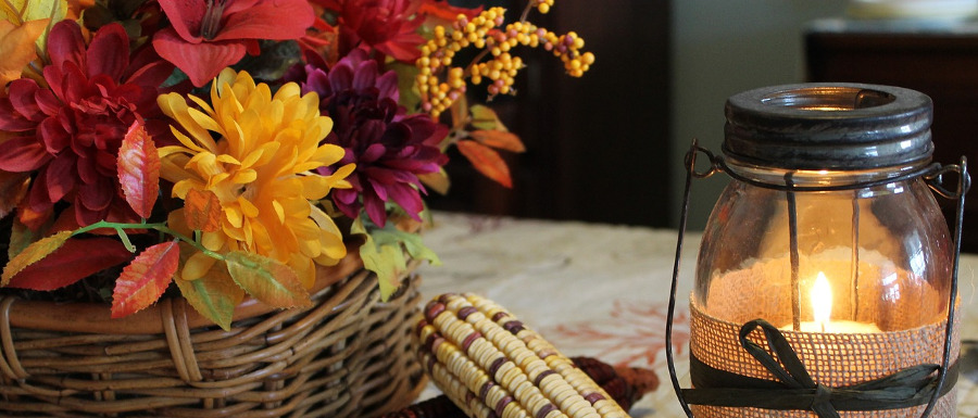 harvest flower arrangements and candle on a table