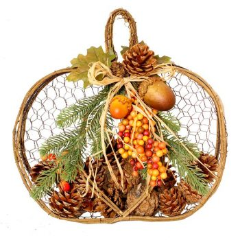 autumn pumpkin decoration full of artificial berries, pine cones and acorns